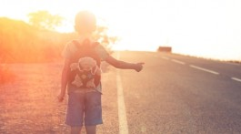 Lost child standing on the road hitchhiking on a sunset