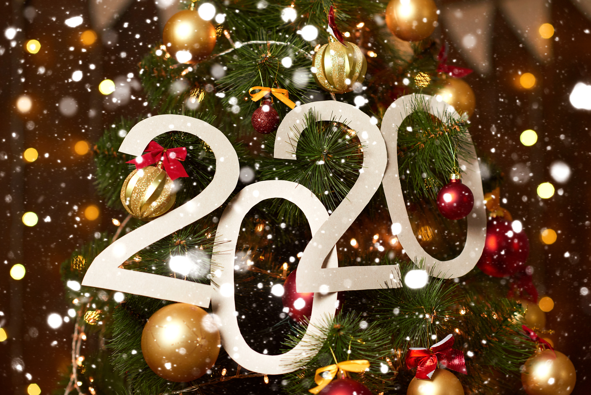 2020 numbers on christmas tree with decoration and wood background - new year holiday concept