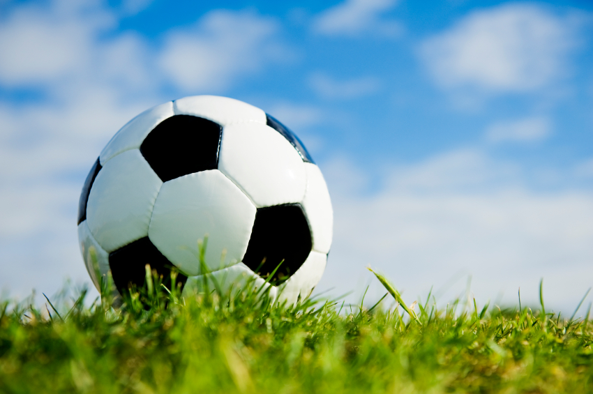 Soccer ball on grass with sky background