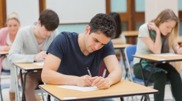 Students sitting in an exam hall doing an exam in university