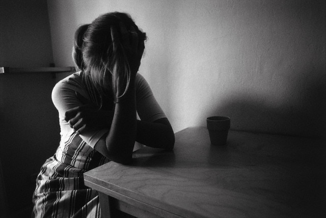Female teenager sitting at table with head in hands --- Image by © Susanne Borges/A.B./Corbis