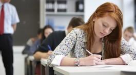 Teacher watching over teenagers in classroom