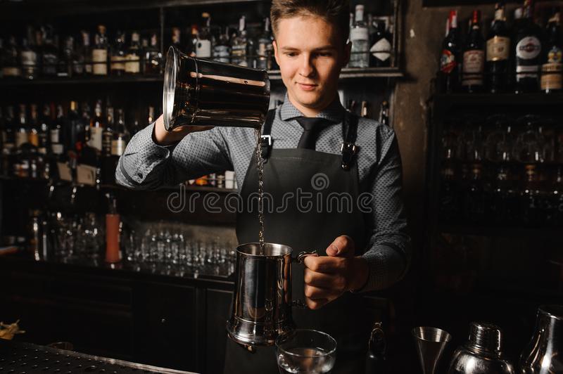молодой-бармен-лить-ясный-алкогольный-напиток-на-счетчике-бара-104311215