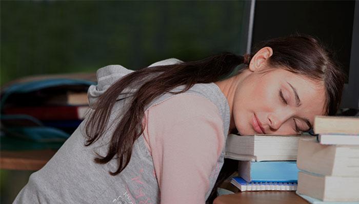 Teenage girl at computer with books sleeping