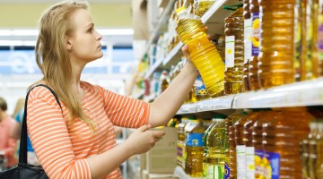 Young woman buys sunflower oil
